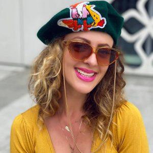 Zielony beret z rysunkową aplikacją na przedzie.